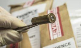 Criminalistic laboratorium, Naukowy funkcjonariusz policji trzyma pocisk porady z pincetami dla balistycznej analizy zdjęcie royalty free