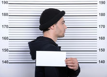 Criminality. Busted burglar. Angry burglar holding a white poster while standing against police line-up stock image