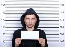 Criminality. Busted burglar. Angry burglar holding a white poster while standing against police line-up royalty free stock photo
