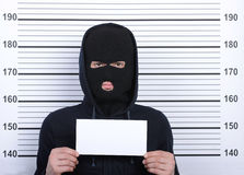 Criminality. Busted burglar. Angry burglar holding a white poster while standing against police line-up royalty free stock images
