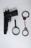 Criminality Concept. Gun and Handcuffs on a White Background stock images