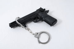 Criminality Concept. Gun and Handcuffs on a White Background royalty free stock photography