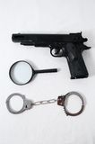 Criminality Concept. Gun and Handcuffs on a White Background royalty free stock photo