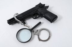 Criminality Concept. Gun and Handcuffs on a White Background royalty free stock images