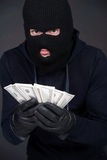Criminality. Criminal in a balaclava holding a fistful of money conceptual of the loot from a robbery bribe corruption coercion payoff ransom or mob protection royalty free stock image
