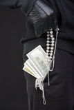 Criminality. Criminal in a balaclava holding a fistful of money conceptual of the loot from a robbery bribe corruption coercion payoff ransom or mob protection Royalty Free Stock Photography
