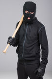 Criminality. Hooligan with baseball bat ready for fight. gray background stock photos