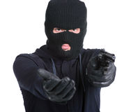 Criminality. Masked robber with gun aiming into the camera against a white background stock images