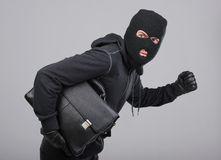 Criminality. Portrait of running male burglar with a handbag. Isolated on gray background royalty free stock images