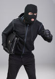 Criminality. Portrait of running male burglar with a handbag. Isolated on gray background stock photography
