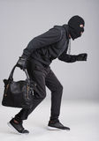 Criminality. Portrait of running male burglar with a handbag. Isolated on gray background royalty free stock photography