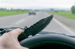 Crimine, uomo, conducente un'automobile che tiene un coltello immagine stock libera da diritti