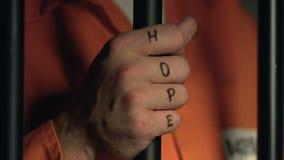 Criminel avec le mot d'espoir sur les barres battues de cellules de participation de poings, violence en prison banque de vidéos