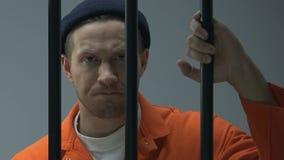 Criminel caucasien regardant la caméra par des barres de prison, jugement de attente banque de vidéos