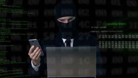 Criminel dans le costume et passe-montagne déchiffrant le code de sécurité utilisant l'ordinateur portable et le téléphone banque de vidéos