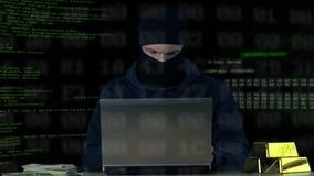 Criminel dans le fonctionnement de passe-montagne sur l'ordinateur portable, entaillant le système de sécurité de banque, code de banque de vidéos