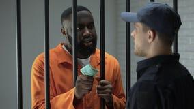 Criminel emprisonné africain donnant d'euro factures au gardien de prison, système défectueux clips vidéos