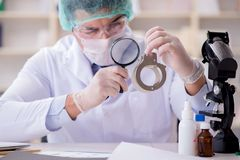 The criminologist police chemist looking at crime evidence. Criminologist police chemist looking at crime evidence stock photo