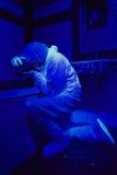Criminologist at work under UV light Royalty Free Stock Photo