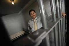 Criminoso atrás das barras na cadeia fotografia de stock royalty free