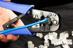 Crimp χεριών ένας στριμμένος συνδετήρας rj-45 ζευγαριού στοκ εικόνες