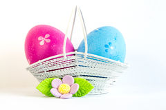 Crimson and blue Easter eggs in a basket with lilac flower Stock Image