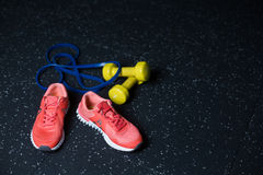 Crimson bright sneakers, yellow vivid dumbbells, blue expander, equipment for a workout on a dark blurred background. Royalty Free Stock Image
