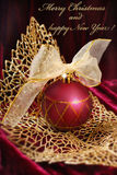 Crimson christmas bauble on golden openwork  leaf Stock Photos