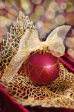 Crimson christmas bauble on golden openwork  leaf Royalty Free Stock Photo