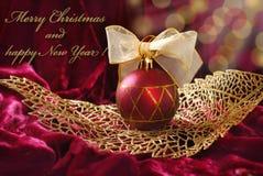 Crimson christmas bauble on openwork golden leaf. Crimson christmas bauble with ribbon on golden openwork leaf Royalty Free Stock Photo