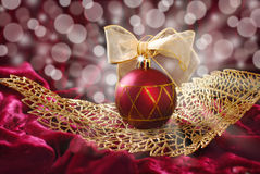 Crimson christmas bauble on openwork golden leaf Royalty Free Stock Images