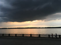 Crimson orange sunset on the river, dark clouds over the city`s waterfront.  Royalty Free Stock Image