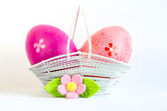 Crimson and pink Easter eggs in a basket with pink flower Royalty Free Stock Photo