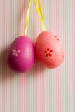 Crimson and pink hanged Easter eggs on striped background Stock Photos