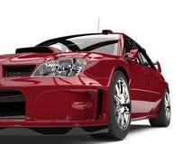 Crimson red modern GT race car - front headlight closeup shot Stock Photo