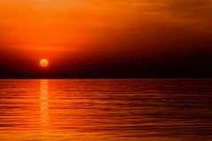 Crimson red sunrise of the orange sun over the ocean. Waves Stock Photography