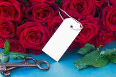 Crimson roses with empty tag Stock Image