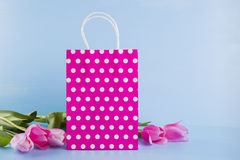 Crimson shopping bag with bouquet of pink tulips on blue wooden Royalty Free Stock Photo