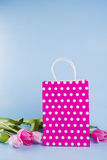 Crimson shopping bag with bouquet of pink tulips on blue wooden Royalty Free Stock Photos