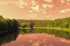 Crimson sky reflection. Clouds reflect in the water stock photography