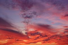 The crimson sunset and amazing clouds in the sky. View of the crimson sunset and amazing clouds in the sky Royalty Free Stock Image