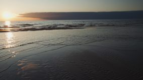 Crimson sunset with clear sky and mirror like reflections in water - Ribbed sand and waves - Tuja, Latvia - April 13 stock footage