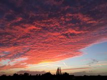 Crimson sunset over yorkshre. Orange gold and red sunset with high clouds Stock Photo