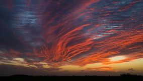 Crimson, windblown clouds at sunset. Crimson coloured clouds stretched by very strong winds. Sun setting over the flat fenlands of Lincolnshire, UK Royalty Free Stock Image