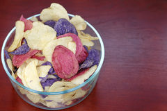 Crimson, Yellow and Purple Potato Chips. Crimson, Purple Majesty and Chipeta or Atlantic potato chips in a glass bowl on a wood table. Potato chips variety stock photo