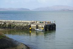 Crinan harbour basin wall and inflatable boat clear sea in Argyll and Bute Scotland. Uk royalty free stock images