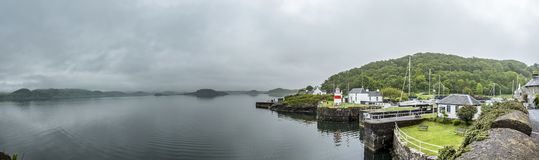 Crinan , Scotland - May 24 2017: Lighthouse welcoming ships and vessels to the locks of Crinan Canal. CRINAN , SCOTLAND - MAY 24 2017: Lighthouse welcoming boats Royalty Free Stock Image