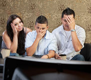 Cringing Family at Television. Disappointed Hispanic family sitting in front of television Stock Image