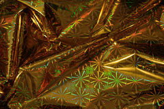 Crinkled wrapping paper background. Crinkled gold wrapping paper reflecting yellow, green and red colors Stock Photography