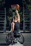 Cripple basketball player in wheelchair plays basketball. Cripple basketball player in wheelchair plays basketball on open air ground Stock Photos